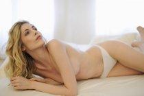 Eine sexy Frau in Unterwäsche liegen und posiert auf einem Bett — Stockfoto
