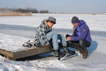 Father and son putting on ice skates near frozen lake in Flevoland, The Netherlands — Stock Photo