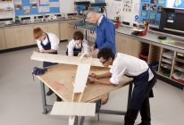 High angle view of teacher and students working on large wooden airplane model in woodworking class — Stock Photo