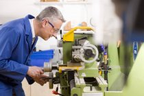 Side view of metalworker in blue lab coat using drill in workshop — Stock Photo