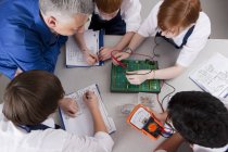 Top view of teacher watching group of students using electronic measuring device at table in vocational class — Stock Photo