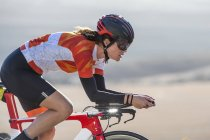 Close-up of female cyclist riding race bicycle on sunny open road — Stock Photo