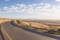 View of long open road at sunrise in arid landscape — Stock Photo