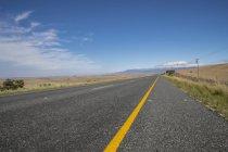 Route de campagne droite menant à travers l'aride paysage sud-africain — Photo de stock