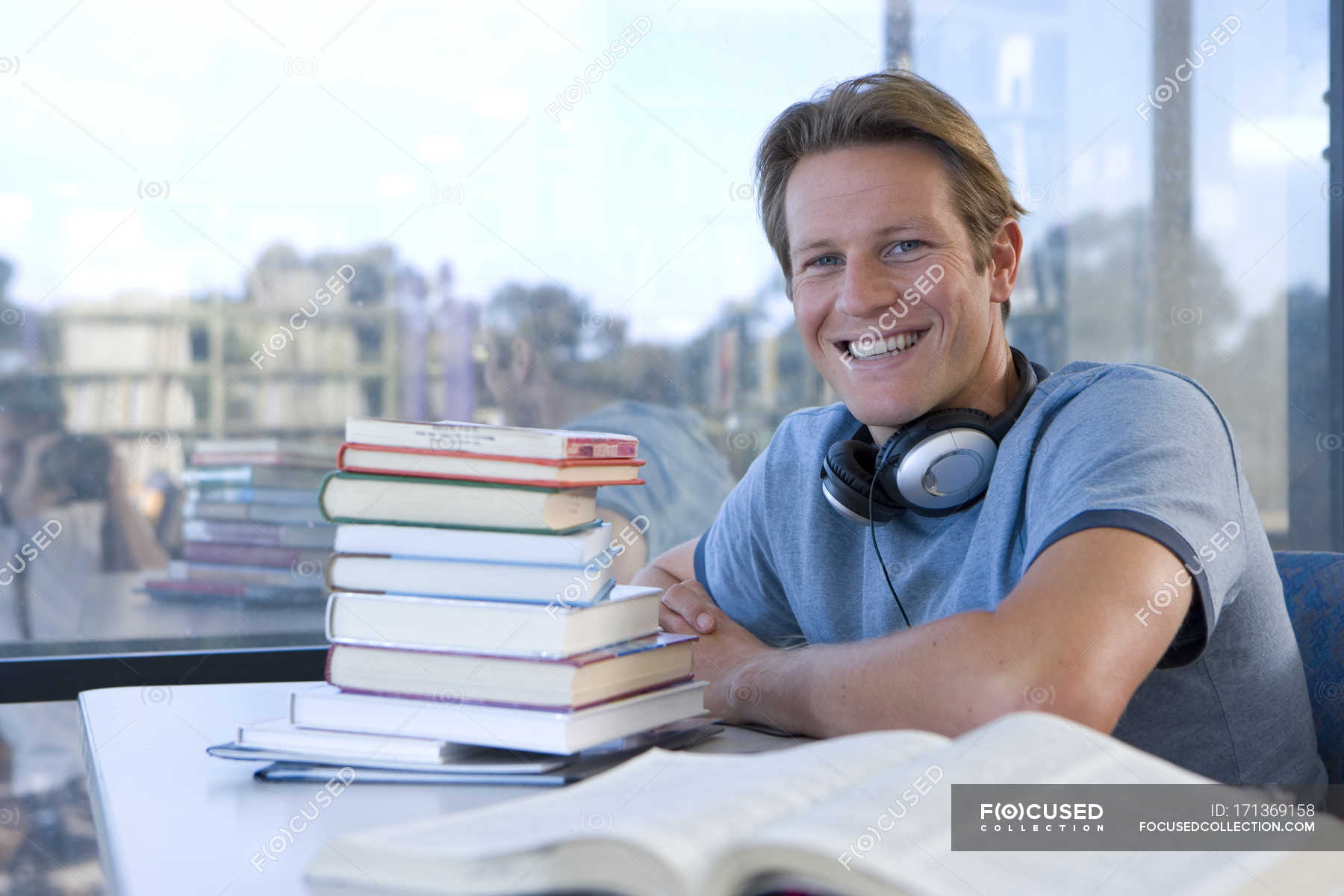 Young Man With Headphones Around Neck Studying Smiling