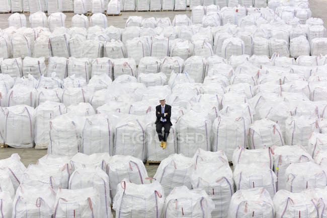 Businessman sitting on top of large bags of recycled plastic pellets in warehouse — Stock Photo