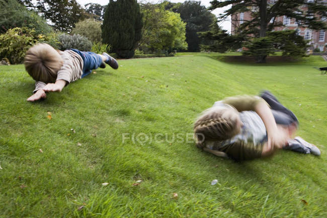 Boy and girl rolling down grassy slope in large country garden — Stock Photo