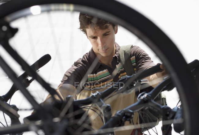Человек, ходить по магазинам для нового велосипеда в магазин велосипедов, просматривать через колесо, фокус на фоне — стоковое фото