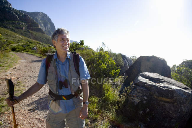 Smiling mature man with rucksack and hiking pole, hiking on mountain trail — Stock Photo