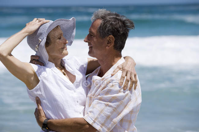 Side view of senior couple embracing on beach — Stock Photo