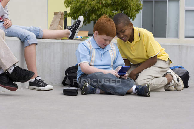 Children sitting on wall outside school, two boys sitting on ground playing video game — Stock Photo