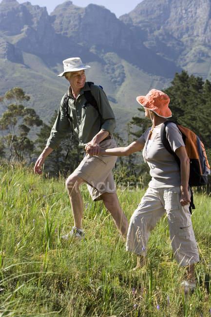 Coppie maggiori con zaini e cappelli da sole escursioni sul fianco di una montagna e che tengono le mani — Foto stock