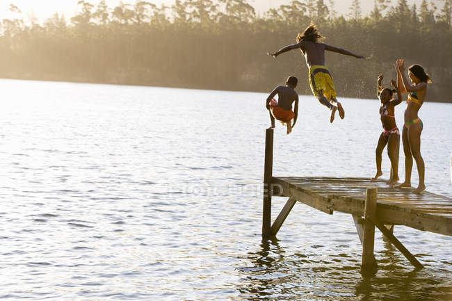 Father and son in swimwear jumping off jetty into lake at sunset, mother and daughter cheering — Stock Photo