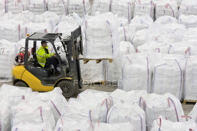Forklift operator lifting large bag of recycled plastic pellets in warehouse — Stock Photo