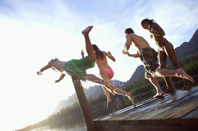 Quatre jeunes adultes, plongée depuis la jetée dans le lac par journée ensoleillée — Photo de stock