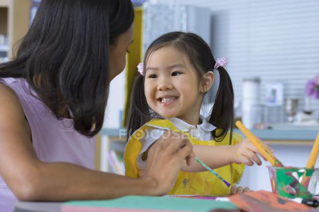 Vista frontale dell'insegnante che aiuta la ragazza pittura allo scrittorio in aula — Foto stock
