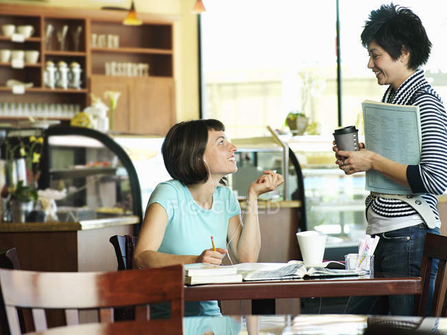 Two women talking in cafe, woman studying at table — Stock Photo