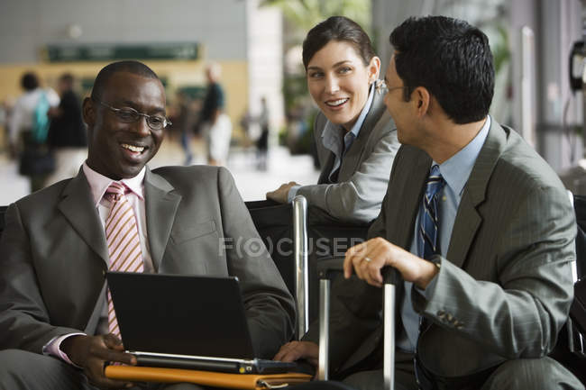 Three business people talking in airport terminal, businessmen with laptop and luggage — Stock Photo