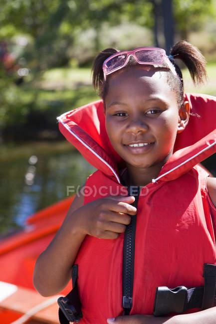 Ragazza indossa giubbotto rosso e sorridente con sfondo sfuocato — Foto stock