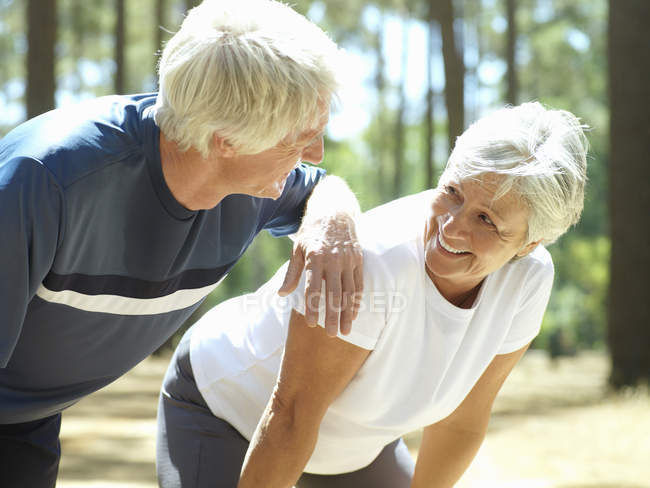 Senior couple in sportswear leaning on knees — Stock Photo