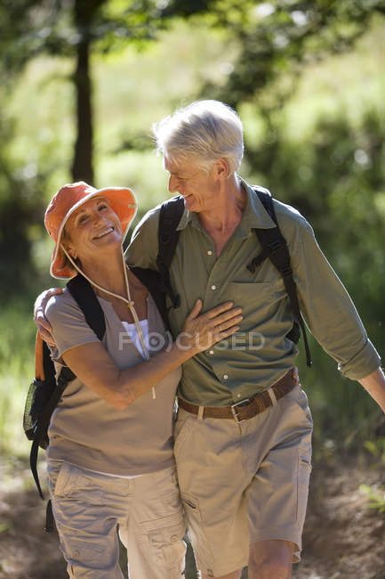 Senior couple with rucksacks hiking along woodland trail, arms around each other — Stock Photo
