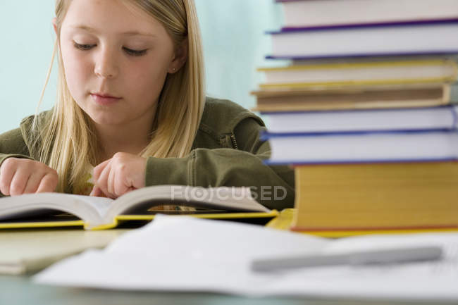 Girl reading textbook at desk in classroom — Stock Photo