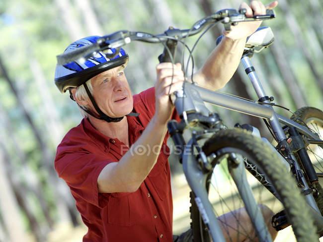 Homme senior actif en casque vélo vélo de vérification — Photo de stock