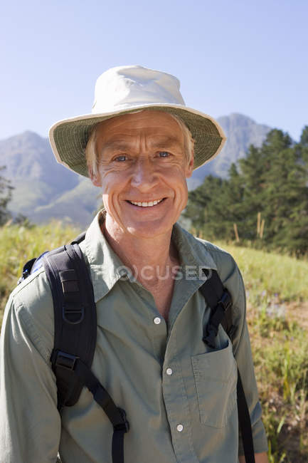 Portrait of senior man with rucksack and sun hat standing on hiking trail in mountains — Stock Photo