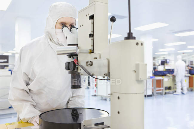 Scientist in clean suit using microscope in silicon wafer manufacturing laboratory — Stock Photo