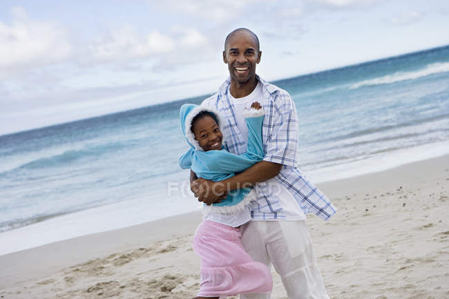 Father hugging daughter at sand beach — Stock Photo