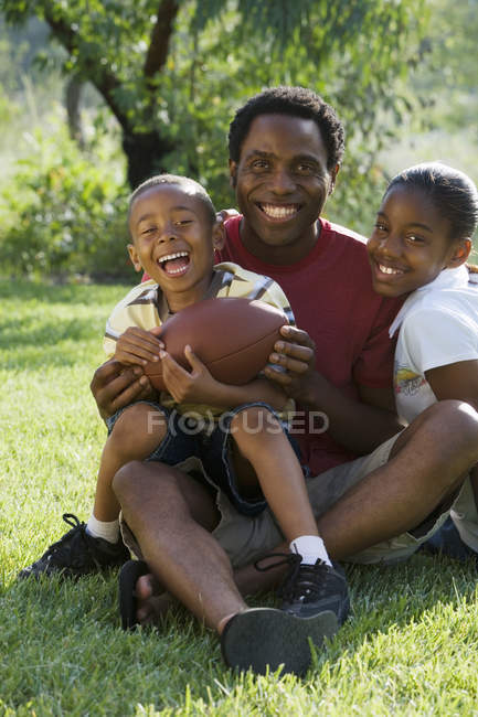Boys sitting on fathers laps and holding american football in park — Stock Photo