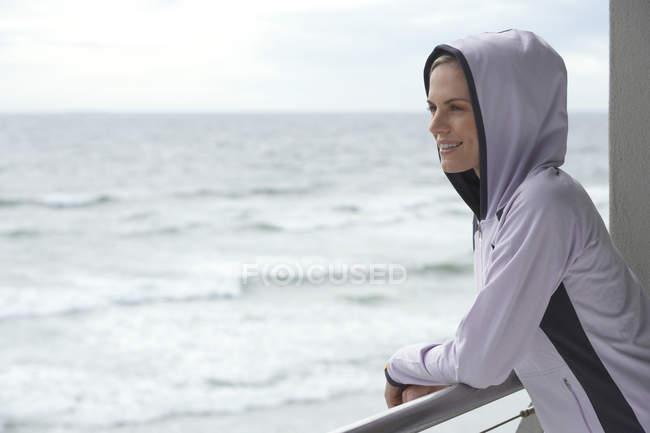 Vue latérale d'une femme portant cagoule haut debout sur le balcon et regardant horizon — Photo de stock