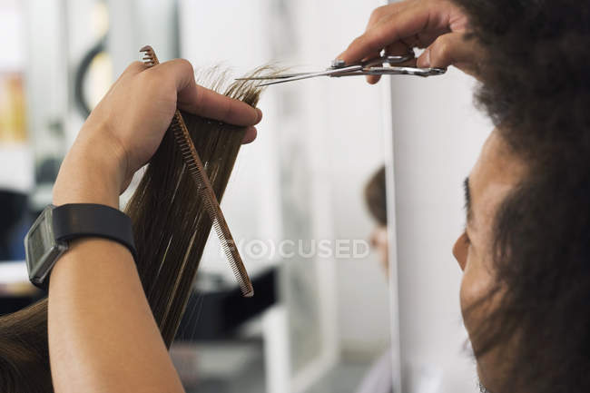 Rear view of young male hairdresser cutting woman hair in salon — Stock Photo