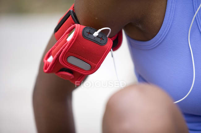 Female jogger wearing MP3 player strapped to arm in red case, mid-section — Stock Photo