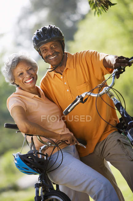 Active senior couple standing with bicycles in park — Stock Photo