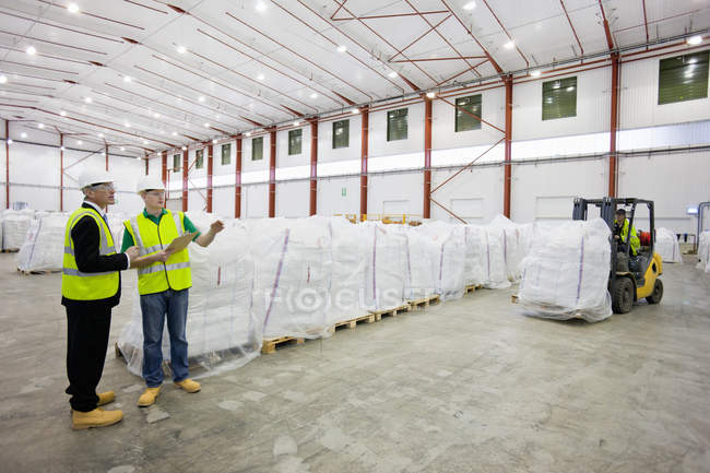 Businessman and workers among large bags of recycled plastic pellets in warehouse — Stock Photo