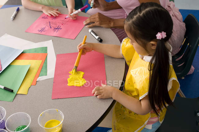 Elevato vista della ragazza pittura su pezzo di carta allo scrittorio in aula — Foto stock
