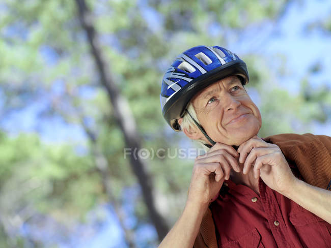 Low angle view of active senior man adjusting strap on cycling helmet — Stock Photo