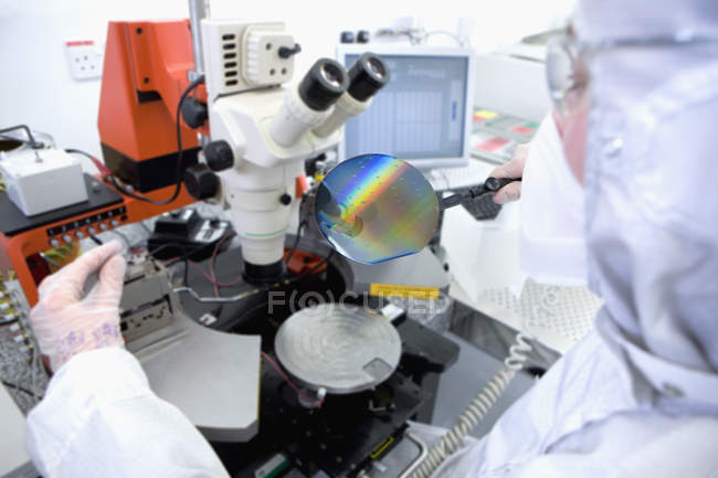 Scientist in clean suit examining silicon wafer under microscope in clean room laboratory — Stock Photo