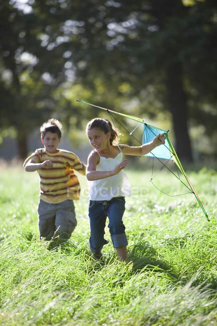 Ragazzo e ragazza che gioca con il cervo volante in campo — Foto stock