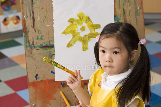 Girl painting picture of yellow flower on easel in classroom — Stock Photo