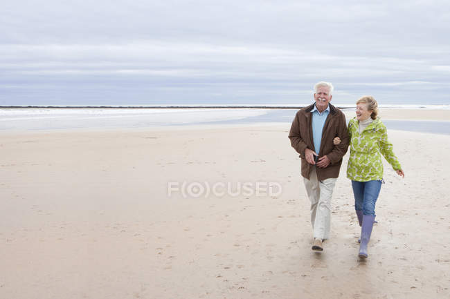 Mature couple walking on sand beach with sea on background — Stock Photo