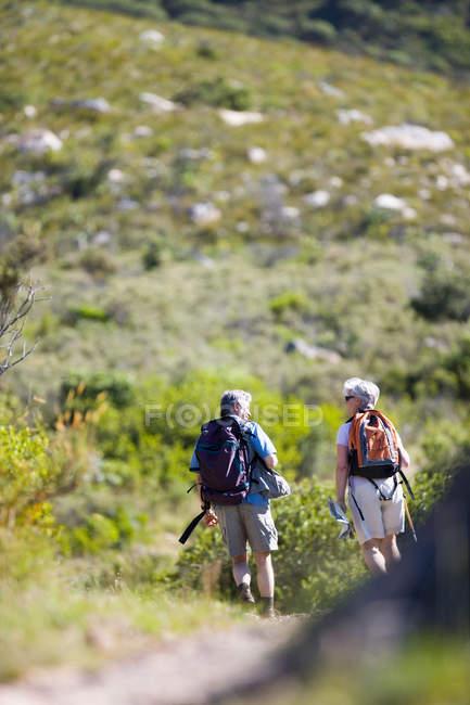 Rear view of senior couple with rucksacks hiking on mountain trail — Stock Photo