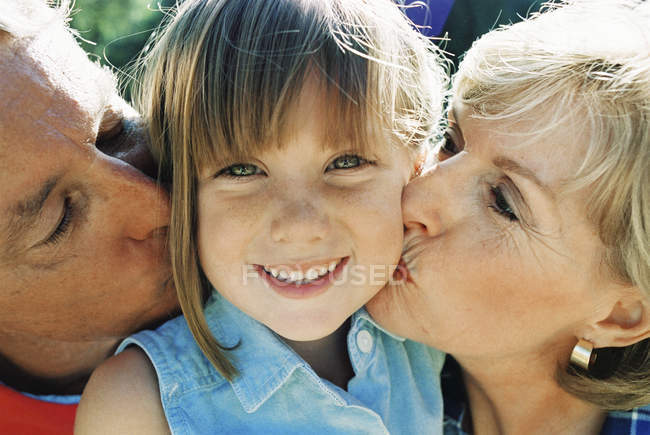 Front view of grandparents kissing granddaughter — Stock Photo