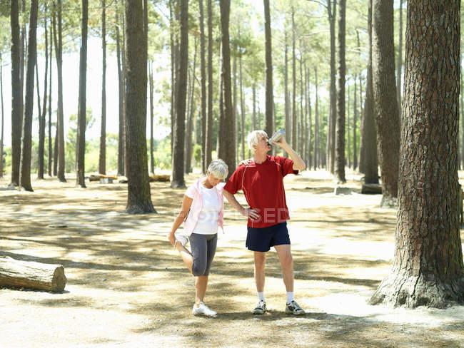 Активные Пожилые супружеские пары, в спортивной одежде принимая перерыв с бегом, женщина, растяжения при человек питьевой воды — стоковое фото