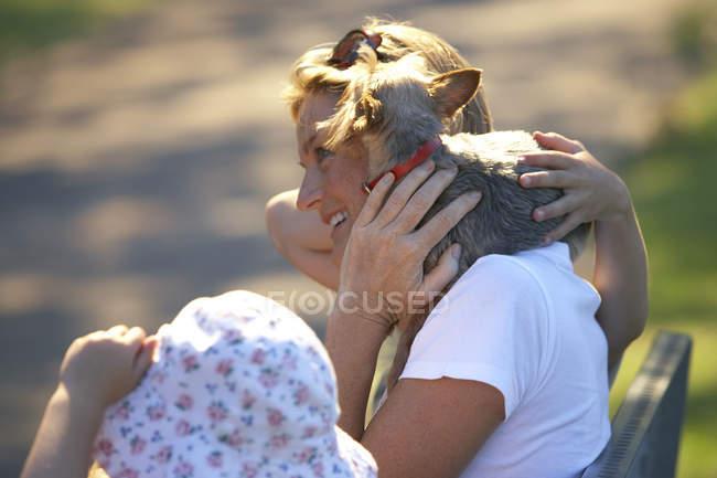 Зрелые женщины, поддерживая собака на плече, сосредоточиться на фоне — стоковое фото