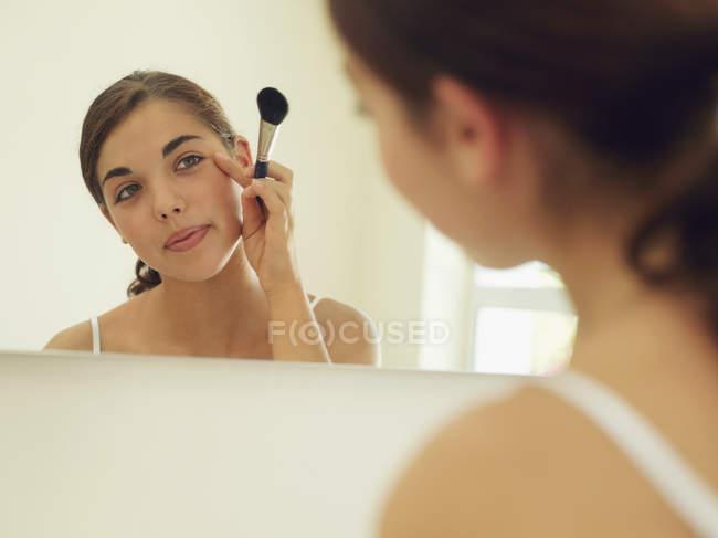 Girl applying make-up with brush — Stock Photo