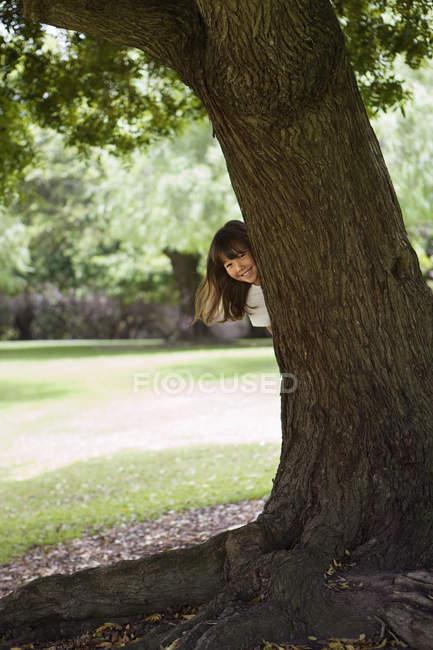 Mädchen versteckt sich hinter Baumstamm im Garten und lächelnd — Stockfoto