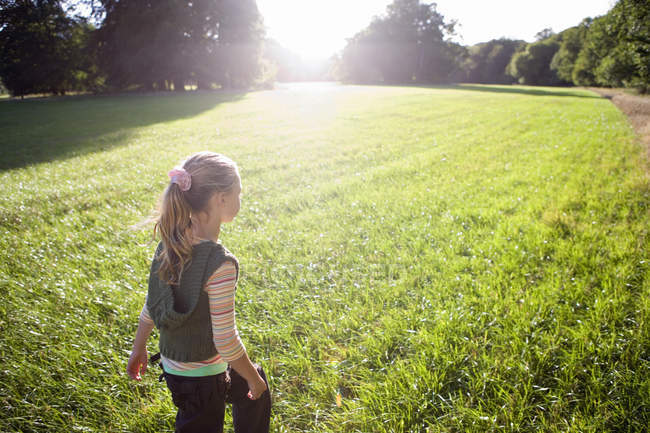Vista traseira da menina loira andando no campo na luz solar brilhante, árvores no fundo — Fotografia de Stock