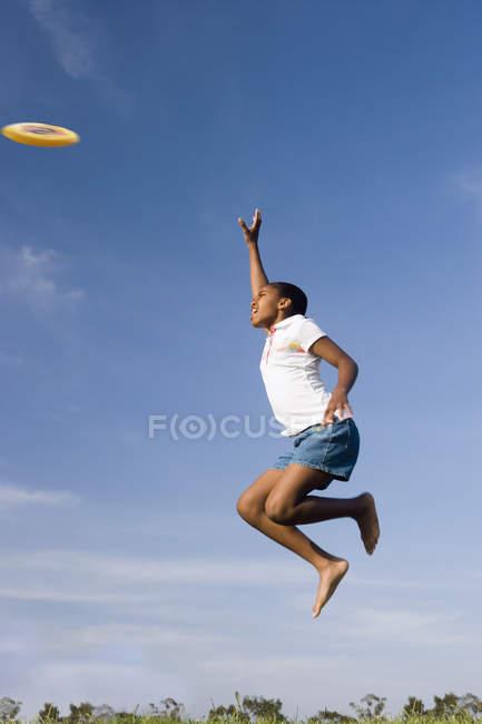 Низький кут зору дівчина, стрибки в повітря, намагаючись зловити фрісбі — стокове фото